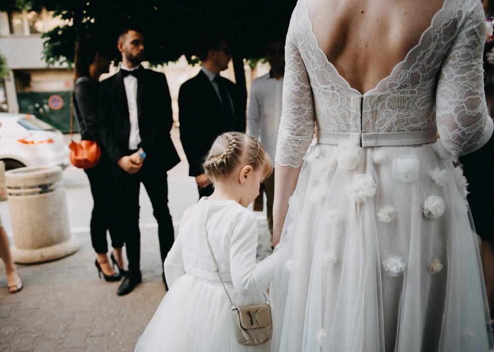 Little bridesmaid walking beside bride in Novi Sad town center