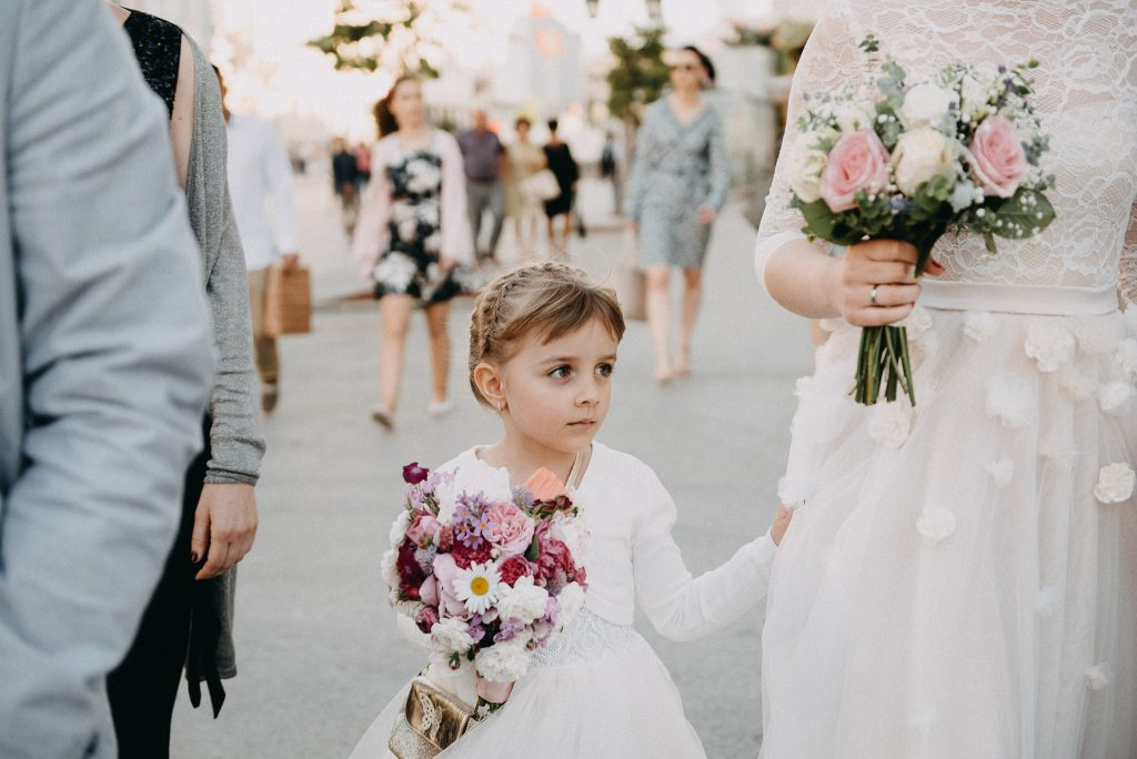 Little bridesmaid walking beside bride in Novi Sad town center
