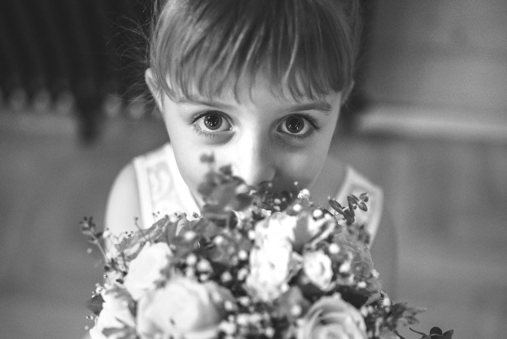 Little bridesmaid holding a wedding bouquet and smiling in Loft Lounge and Bar Novi Sad