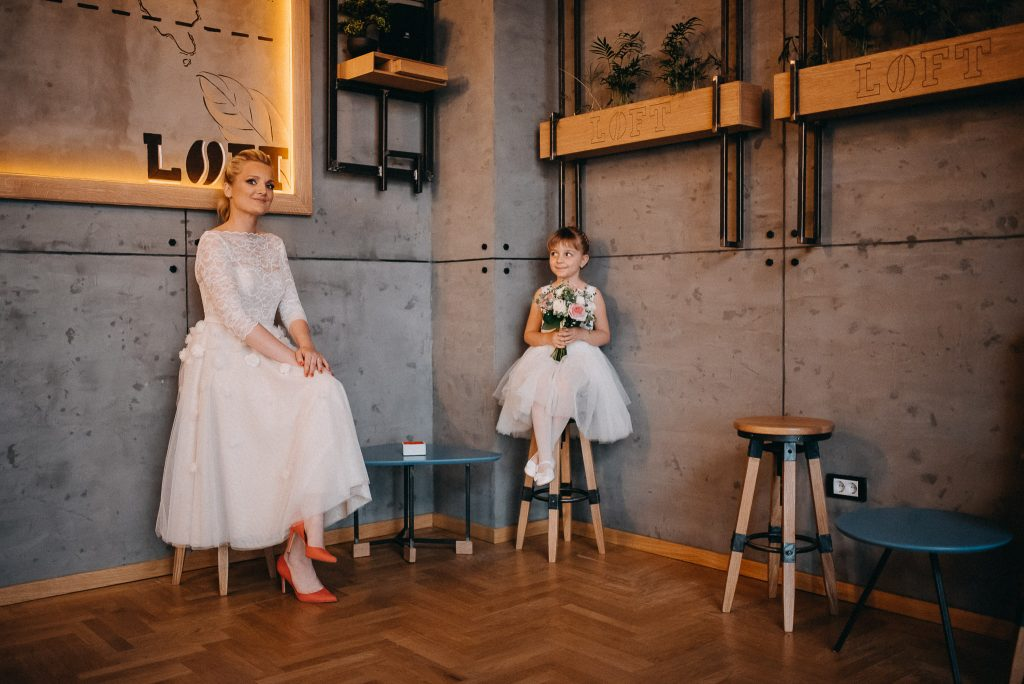 Bride and bridesmaid holding a wedding bouquet and smiling in Loft Lounge and Bar Novi Sad